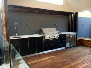 outdoor kitchen with timber decking and glass fence in bayside suburb of melbourne