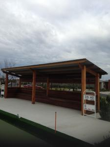 Covered timber pergola and seating for bowlers