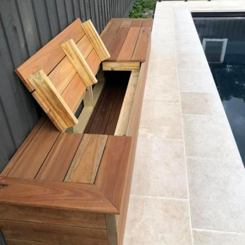 Timber swimming pool seat with lid open for storage