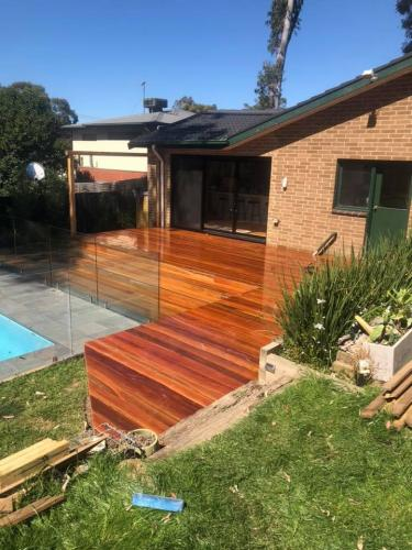 Timber decking leading to swimming pool with glass fence