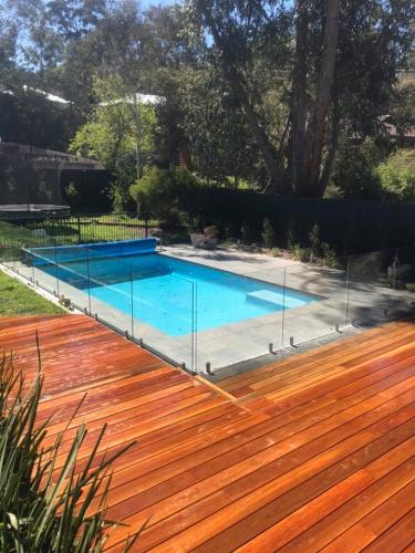 Timber decking surrounding swimming pool with glass pool fence